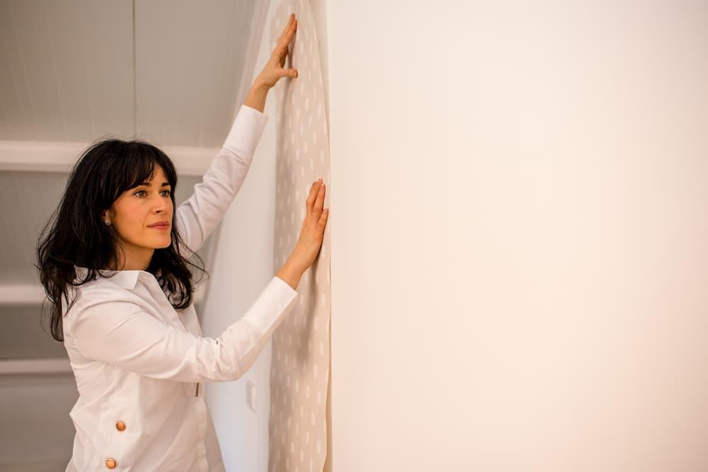 Imagen de Virginia González decorando un inmueble pegando papel en una pared