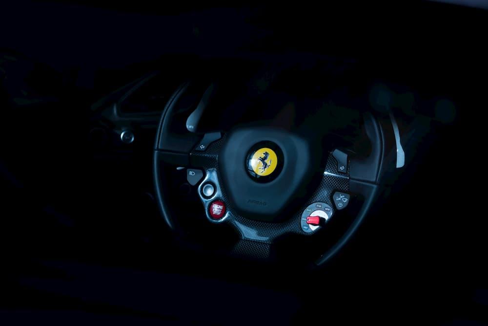 Imagen del volante de un Ferrari en fondo negro.