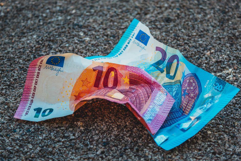 Imagen de dos billetes de 20 y 10 euros tirados en el suelo