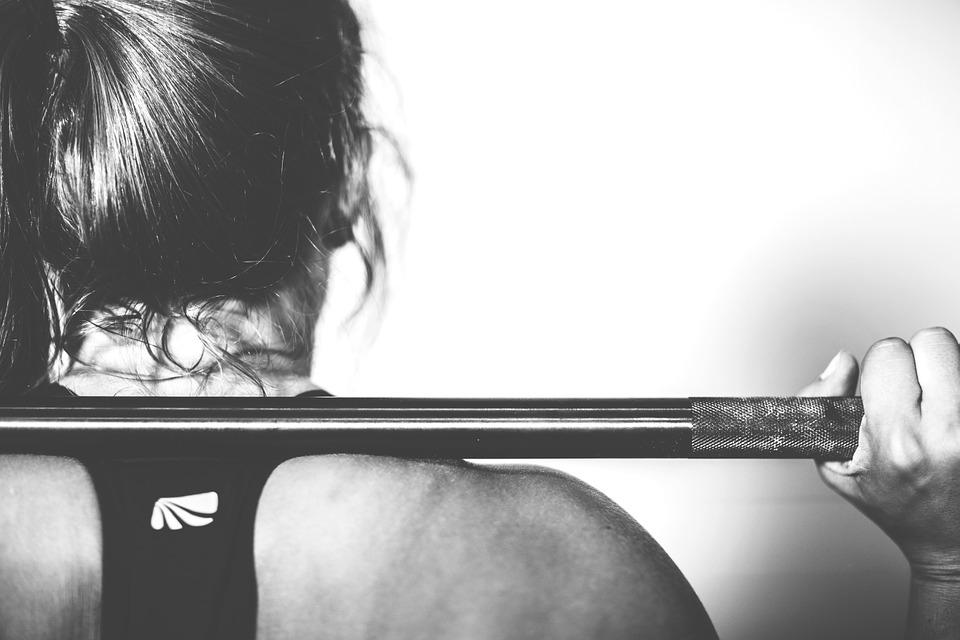 Imagen de una chica levantando una barra de gimnasio