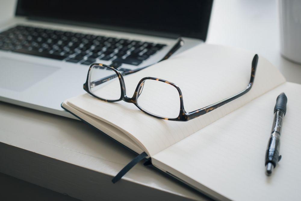 Imagen de unas gafas apoyadas sobre una libreta en un escritorio