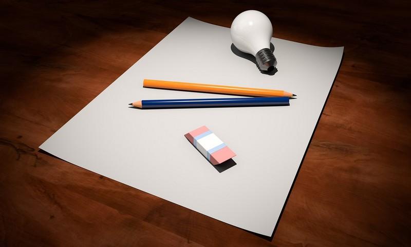 Hola en blanco con lápices y una bombilla encima