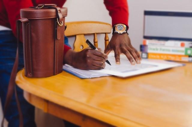 Un hombre de raza negra firmando un contrato en una mesa