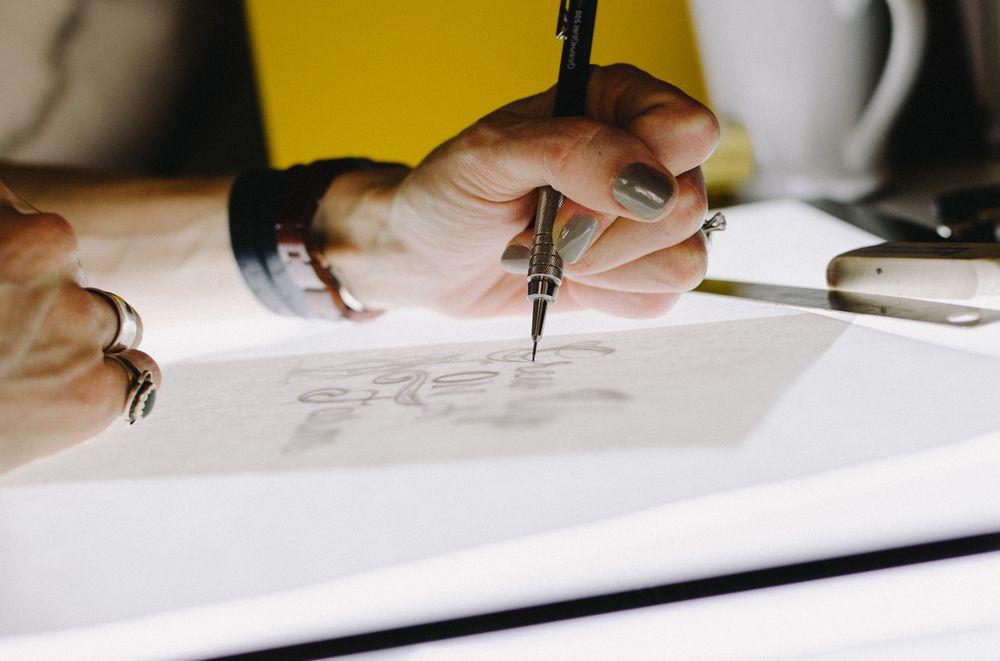 Imagen de una mujer dibujando en su mesa de trabajo