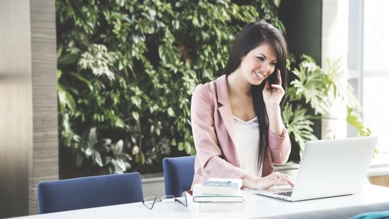 Una mujer hablando por teléfono gestionando proyectos con un portátil