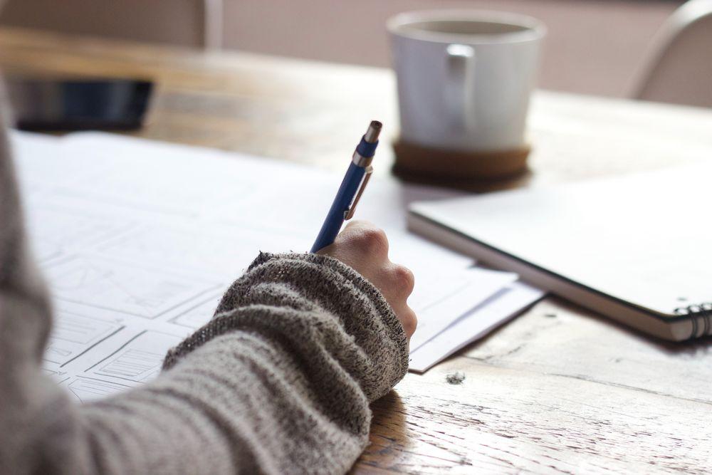 Imagen de una persona escribiendo apoyada en una mesa de madera
