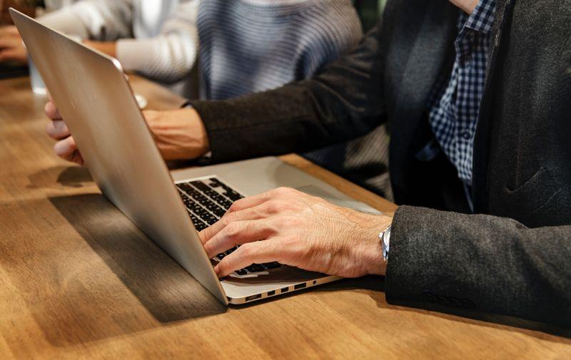 Imagen de una persona usando un portátil para lograr el registro de dominios .ES y .COM